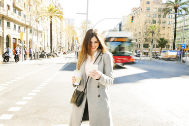 Spain, Barcelona, smiling young woman with coffee to go standing at roadside looking at cell phone - VABF01580