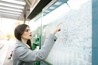 Spain, Barcelona, young woman looking at map at station - VABF01583