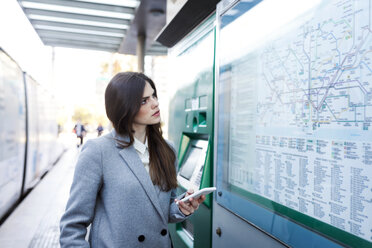 Spain, Barcelona, young woman with smartphone looking at map at station - VABF01586