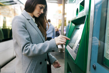 Spain, Barcelona, woman buying ticket from automated machine at  station - VABF01589