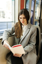 Portrait of young woman reading book in tramway - VABF01595