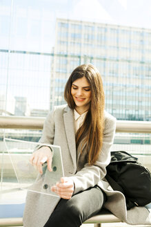 Spain, Barcelona, portrait of smiling young businesswoman using futuristic portable device at station - VABF01598