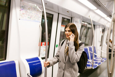 Spain, Barcelona, young woman on the phone standing in underground train - VABF01601