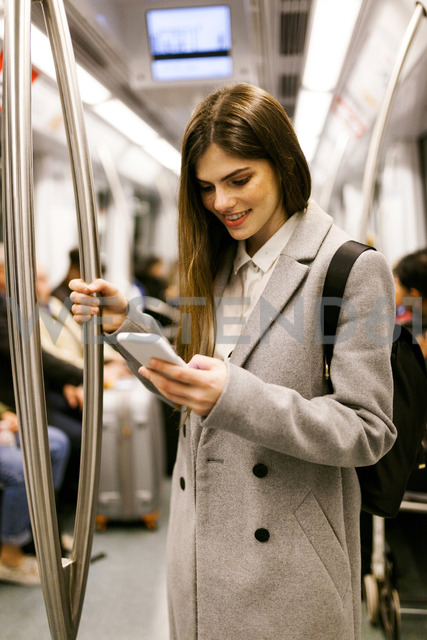 Spain, Barcelona, young businesswoman using cell phone in underground train - VABF01604 - Valentina Barreto/Westend61