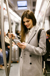 Spain, Barcelona, young businesswoman using cell phone in underground train - VABF01604