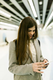 Smiling young woman using cell phone and earphones - VABF01607