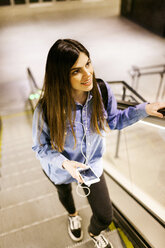 Portrait of smiling young woman standing on escalator listening music with cell phone and earphones - VABF01610