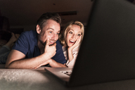 Amazed mature couple lying on couch at home looking at laptop - UUF13486