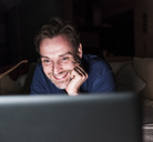 Portrait of smiling man looking at laptop having fun - UUF13489