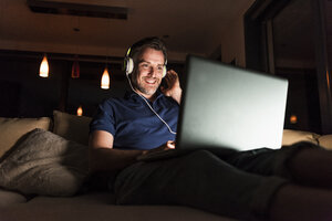 Man with headphones sitting on couch at home looking at laptop - UUF13492