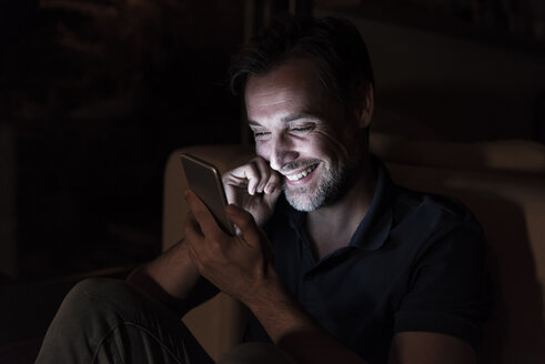 Portrait of happy mature man using cell phone at home - UUF13495
