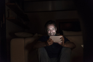 Laughing man sitting in the dark at home looking at smartphone - UUF13498