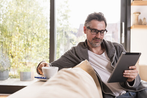 Portrait of mature man with cup of coffee sitting on couch using tablet - UUF13501