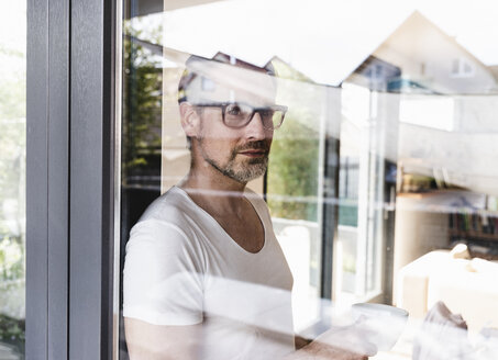 Portrait of pensive man standing behind glass door - UUF13504