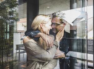 Happy mature couple behind windowpane at home - UUF13510