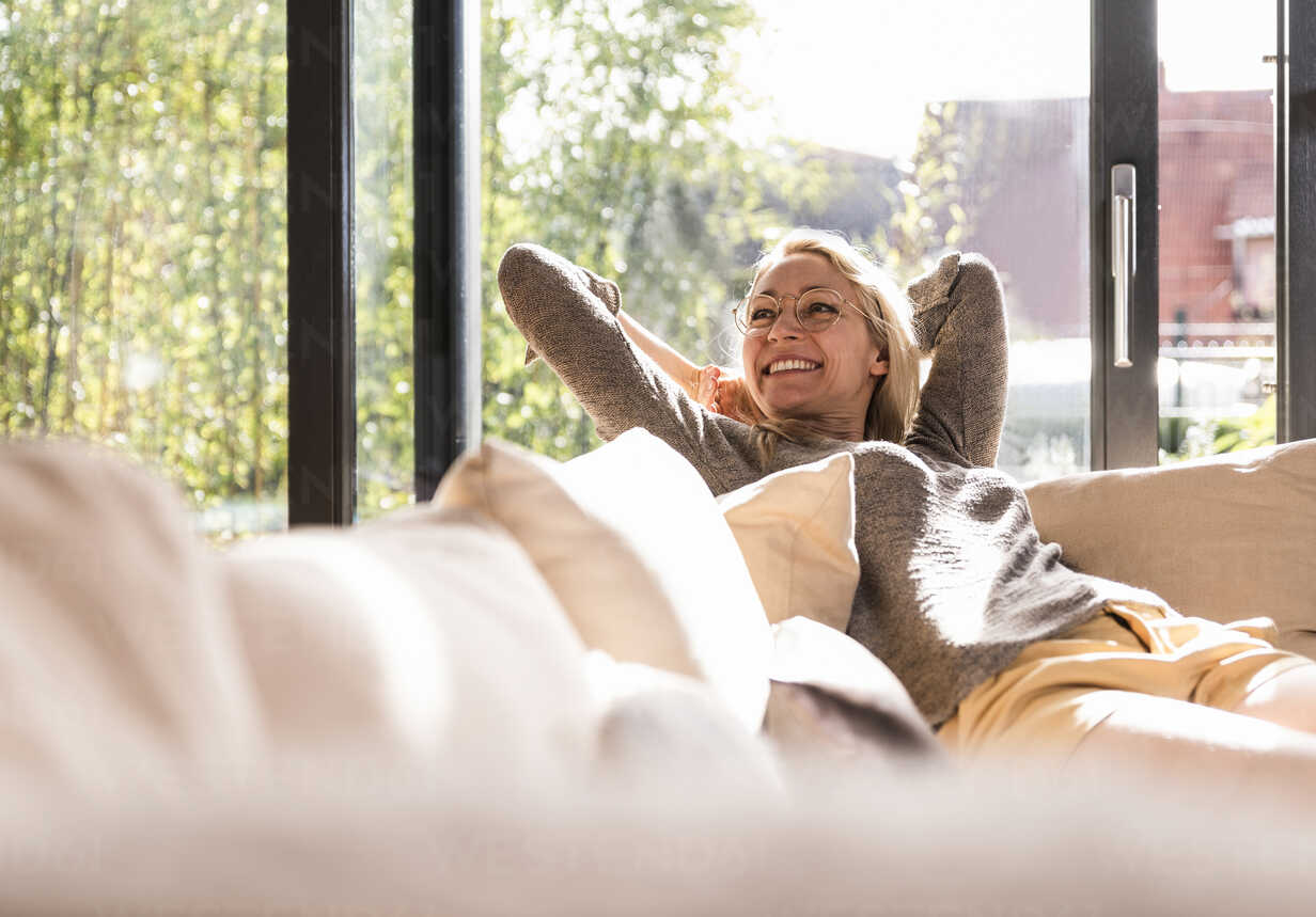 Happy mature woman relaxing on the couch at home - UUF13522 - Uwe Umstätter/Westend61