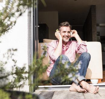 Smiling mature man sitting at open terrace door listening music with headphones - UUF13528