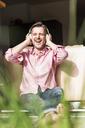 Portrait of mature man sitting at open terrace door listening music with headphones - UUF13531