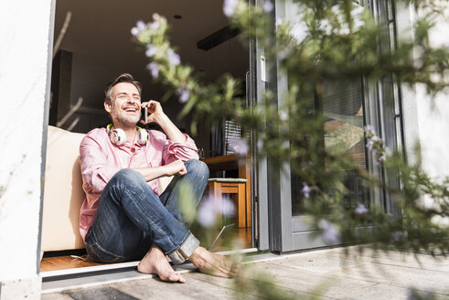 Laughing mature man on the phone sitting at open terrace door - UUF13534