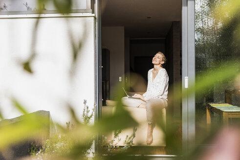 Mature woman with laptop sitting at open terrace door - UUF13540