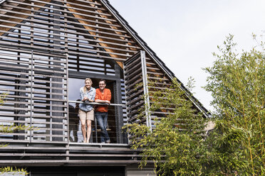 Smiling mature couple standing on balcony of their house - UUF13558
