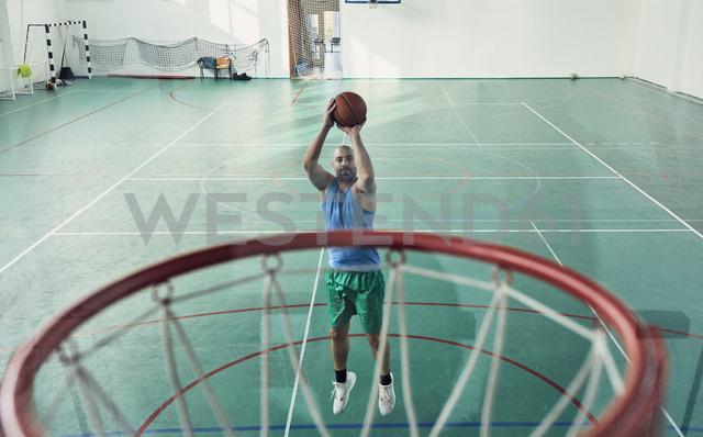 Man playing basketball, basketball hoop, indoor - ZEDF01362