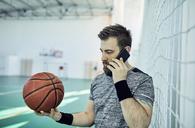 Man with basketball using smartphone, indoor - ZEDF01383