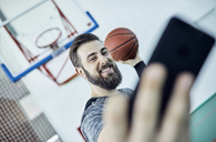 Man with basketball using smartphone, selfie - ZEDF01386