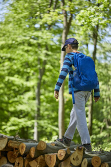 Boy with backpack balancing on logs in forest - ZEDF01403