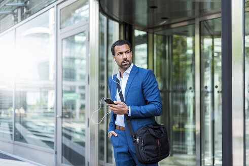 Businessman with smartphone, earphones and laptop bag - DIGF04187