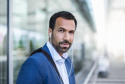 Portrait of businessman with earphones - DIGF04190