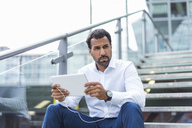 Businessman using tablet, earphone - DIGF04202