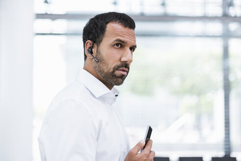 Businessman using smartphone and headset - DIGF04211