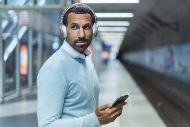 Businessman using smartphone at metro station - DIGF04235