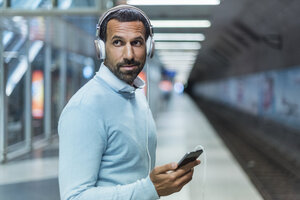 Businessman using smartphone at metro station - DIGF04235