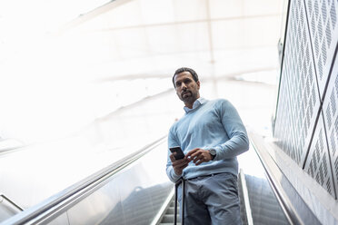 Businessman with smartphone on escalator - DIGF04238