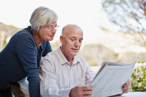 Older couple reading newspaper outdoors - CUF01181