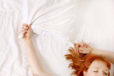 Woman holding on to pillow in bed - CUF01254