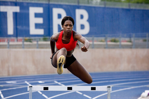 Runner jumping over hurdles on track - CUF01266