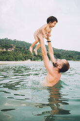 Thailand, Koh Lanta, father playing with his little daughter in the sea - GEMF01928