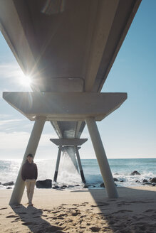 Man standing relaxed under bridge on the beach - SKCF00449