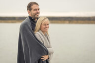 Happy couple standing at lake shore, embracing - PAF01836