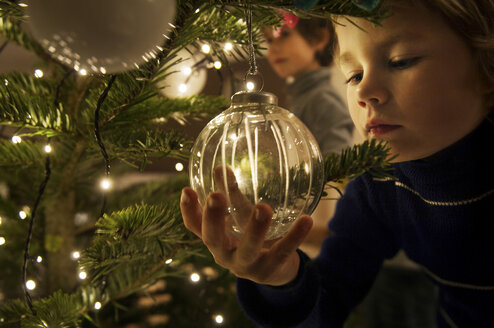Boy decorating Christmas tree with baubles at home - ISF00358