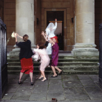 Bride throws the bouquet to hopeful friends - ISF00367