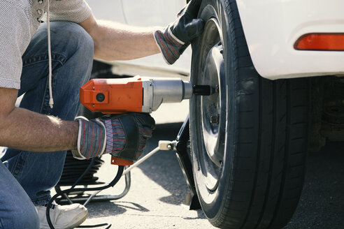 Man changing car tire, partial view - MAEF12575