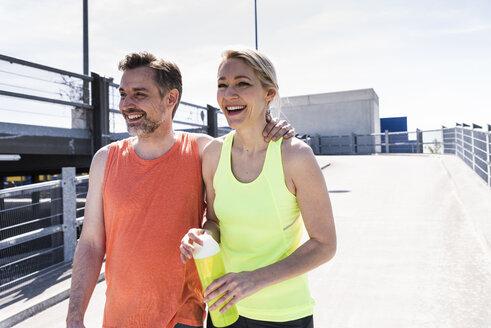Fit couple jogging in the city, having fun, taking a break - UUF13604
