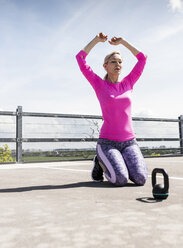 Woman training with dumbells, kneeling on ground - UUF13616