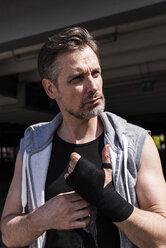 Man bandaging hands for boxing training - UUF13622