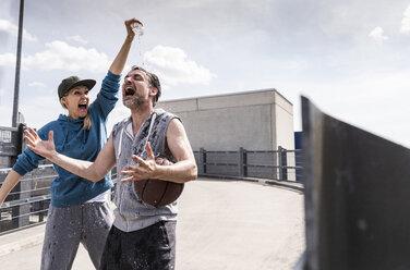 Man and woman playing basketball, splashing water - UUF13643