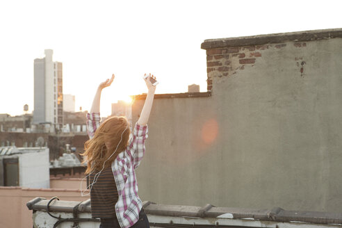 Young woman listening to music with arms raised on city rooftop - ISF00756
